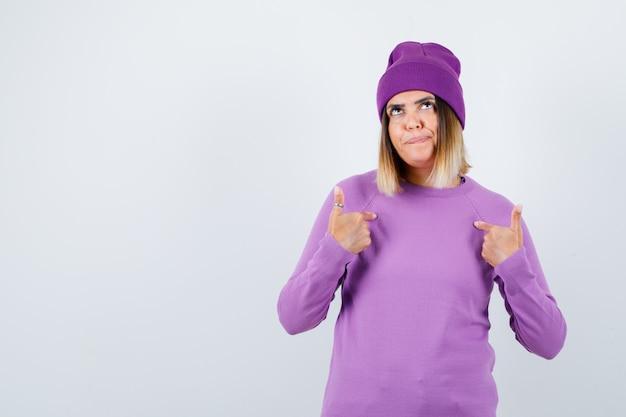 Ritratto di bella signora che indica se stessa in maglione, berretto e guardando fiduciosa vista frontale