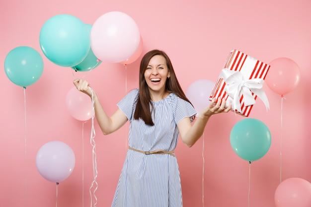 Ritratto di bella donna che ride che indossa abito blu con scatola rossa con regalo regalo e mongolfiere colorate su sfondo rosa brillante. festa di compleanno, concetto di emozioni sincere della gente.