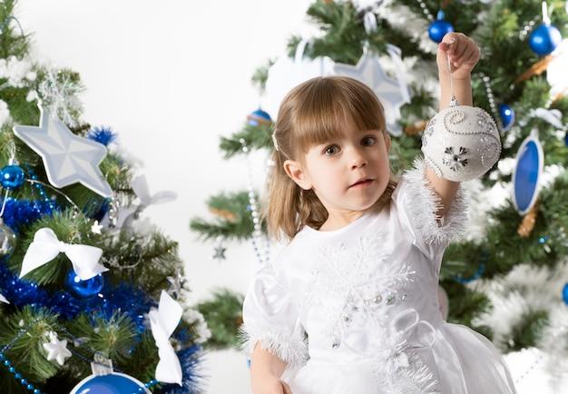 Ritratto di una bella bambina curiosa in posa su uno sfondo di due alberi di capodanno decorati con giocattoli blu