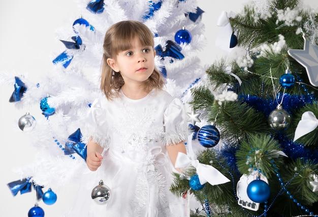 Ritratto di una bella bambina curiosa in posa su uno sfondo di due alberi di capodanno decorati con giocattoli blu.