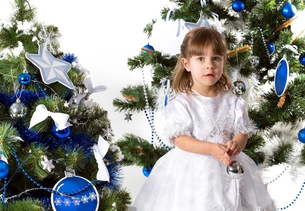 Ritratto di una bella bambina curiosa in posa su uno sfondo di due alberi di capodanno decorati