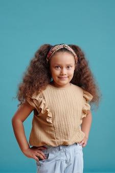 Ritratto di bella bambina che sorride e che posa alla macchina fotografica contro il fondo blu