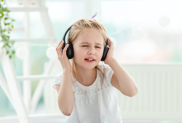 Ritratto di bella bambina che indossa le cuffie al chiuso