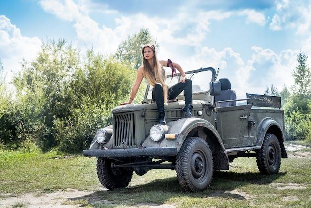 Ritratto di bella donna dai capelli lunghi seduta sul cofano dell'auto