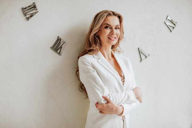 Ritratto di bella donna dai capelli lunghi in giacca da ufficio bianca in posa con le braccia incrociate vicino al muro bianco con orologi.