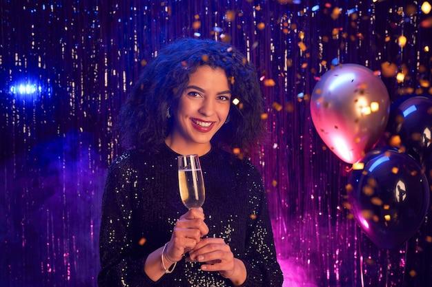 Ritratto di bella donna di razza mista che tiene il bicchiere di champagne e sorride alla macchina fotografica mentre gode della festa in discoteca, copia dello spazio
