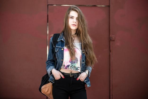 Ritratto di una bella ragazza moderna contro sfondo rosso