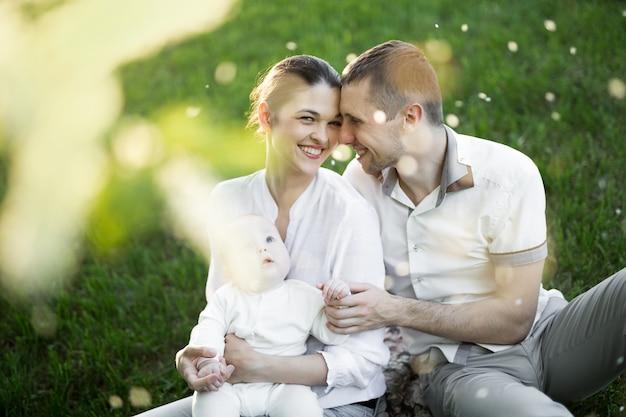 Ritratto bella madre, padre e bambino all'aperto. famiglia felice su un prato estivo
