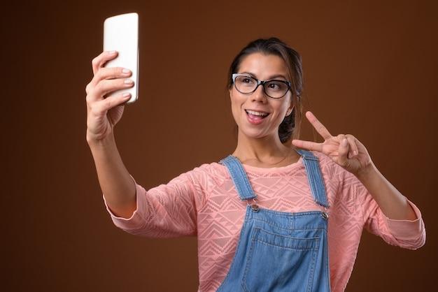 Ritratto di bella donna nerd utilizzando il telefono