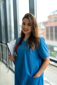 Ritratto di bella infermiera in uniforme blu con appunti in ospedale moderno. concetto medico