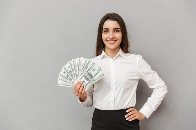 Ritratto di donna bella ufficio con lunghi capelli castani in abbigliamento da lavoro sorridente e in possesso di fan di soldi, isolato sopra il muro grigio