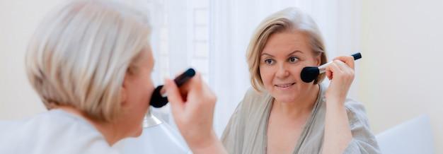 Bella donna anziana del ritratto che tocca la sua pelle perfetta che guarda specchio. close-up maturo viso di donna con pennello toccando la pelle del viso.