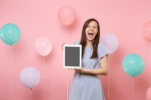 Ritratto di bella donna felicissima con la bocca aperta in vestito blu che tiene il computer tablet pc con schermo vuoto vuoto su sfondo rosa con mongolfiere colorate. concetto di festa di compleanno.
