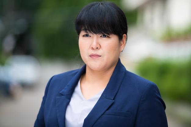 Ritratto di bella donna d'affari asiatica in sovrappeso nelle strade all'aperto