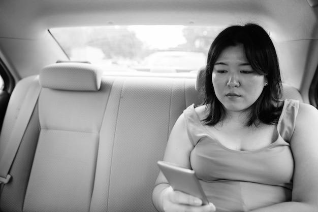 Ritratto di bella donna asiatica in sovrappeso all'interno dell'auto intorno alla città in bianco e nero