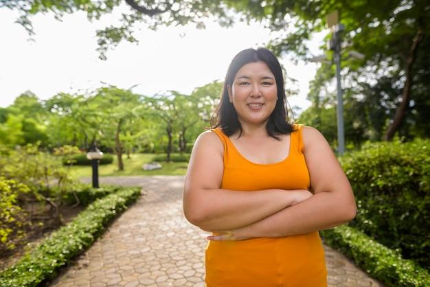 Ritratto di bella donna asiatica in sovrappeso rilassante presso il parco della città di bangkok, thailandia