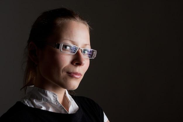 Ritratto di bella donna d'affari pensierosa con gli occhiali