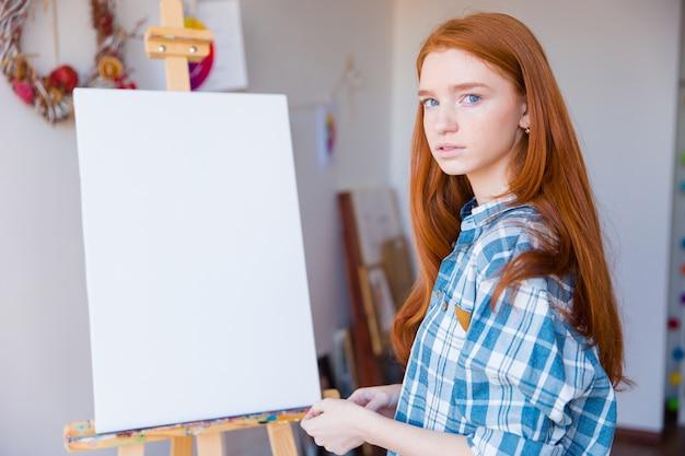 Ritratto di bella giovane donna pensierosa in camicia a scacchi in piedi dentro