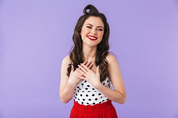 Ritratto di una bella ragazza pin-up che indossa un trucco luminoso in piedi isolata sul muro viola, tifo, festeggia