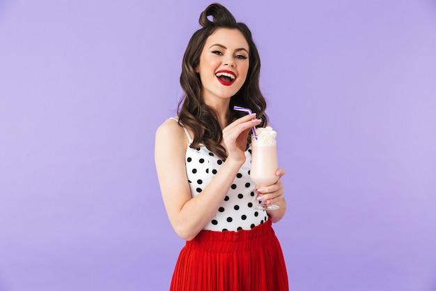 Ritratto di una bella ragazza pin-up che indossa un trucco luminoso in piedi isolata sul muro viola, bevendo frullato