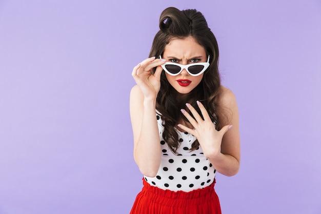 Ritratto di una bella ragazza pin-up che indossa un trucco luminoso in piedi isolata sul muro viola, in posa con occhiali da sole