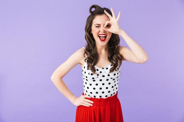 Ritratto di una bella ragazza pin-up che indossa un trucco luminoso in piedi isolata sul muro viola, mostrando ok