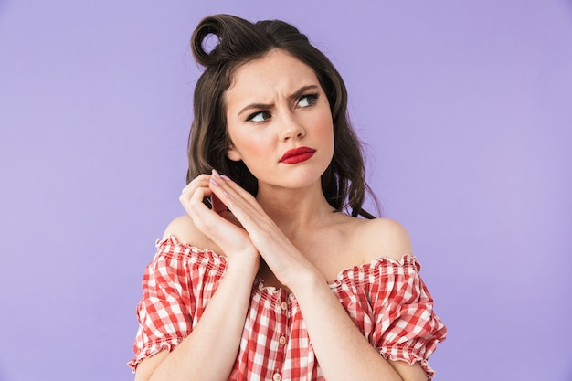 Ritratto di una bella ragazza pin-up che indossa un trucco luminoso in piedi isolata sul muro viola