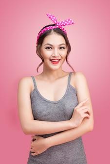 Ritratto di bella donna asiatica pinup con trucco e acconciatura vintage. isolato su sfondo rosa
