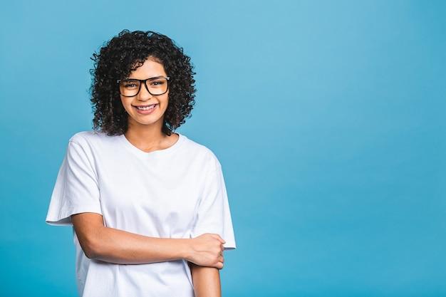 Ritratto di bella donna riccia nera afroamericana positiva in piedi isolato su sfondo blu.