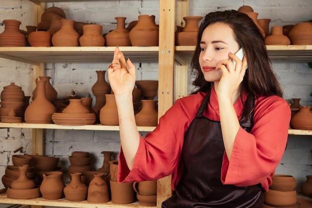 Ritratto di una bella donna vasaio con un telefono. una donna lavora con l'argilla su un tornio da vasaio e parla al telefono. concetto di modellazione artistica dall'argilla