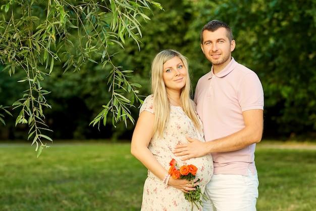 Ritratto di una bella coppia incinta in un parco estivo