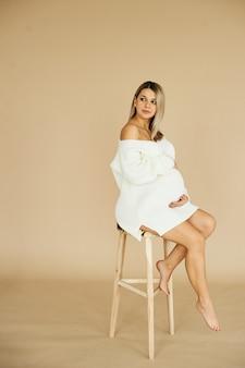 Un ritratto di una bella ragazza incinta vestita di maglione bianco in uno sfondo beige