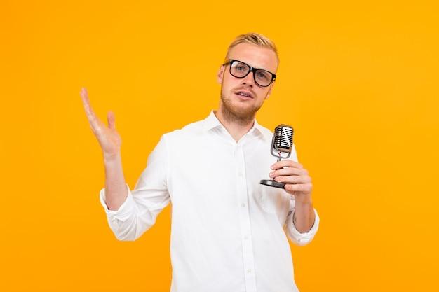 Ritratto di bello presentatore in una camicia bianca con un retro microfono che canta sul giallo