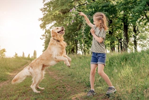 Ritratto di bella ragazza del preteen che gioca insieme con il cane del documentalista dorato all'aperto. ragazza carina con cagnolino nella natura in estate divertendosi