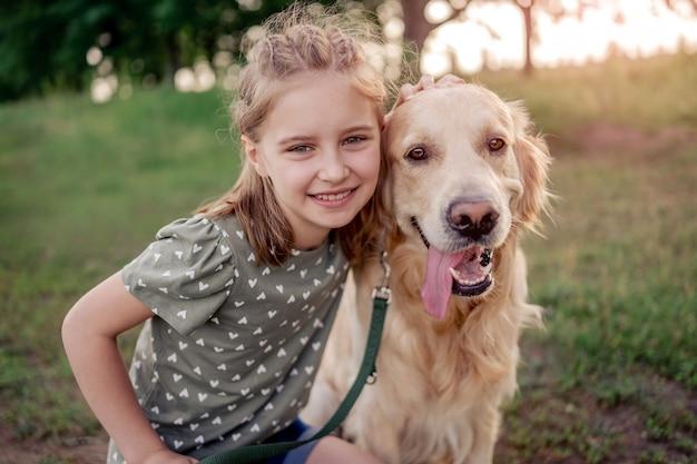 Ritratto di bella ragazza del preteen con il cane golden retriever che guarda l'obbiettivo insieme all'aperto. bambino con cagnolino nel campo in estate