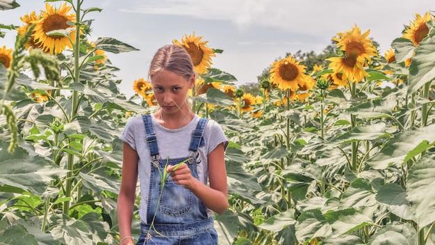 Ritratto di una bella ragazza preteen con i capelli lunghi in un campo di girasoli di girasoli