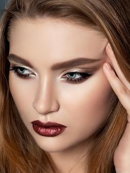 Ritratto di donna bella rossa con trucco da sera, toccando il suo viso. occhi smokey dorati e labbra scure.