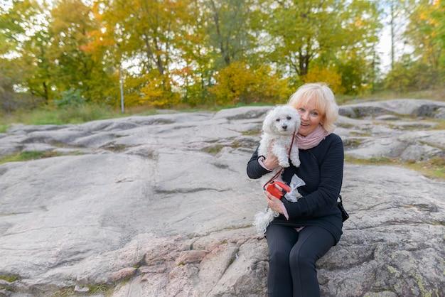 Ritratto di bella donna senior con capelli biondi corti che si distende al parco all'aperto in autunno