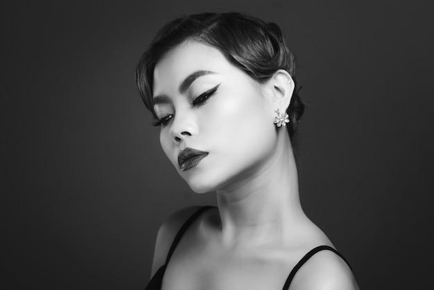 Ritratto di bella donna asiatica sensuale con acconciatura elegante e trucco perfetto.