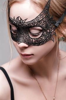 Ritratto di bella donna bionda sensuale con gli occhi verdi nella maschera di pizzo nero su uno sfondo scuro. maschera veneziana
