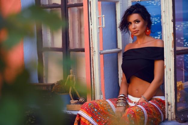 Ritratto di una bella ragazza bruna sensuale, trucco professionale tenero e vestito di moda. stile gipsy.