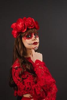 Ritratto di una bella ragazza seria con trucco e abbigliamento dia de los muertos.