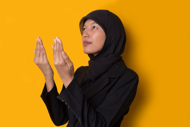 Ritratto di una bella giovane donna musulmana seria che indossa un hijab nero