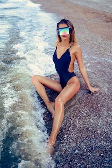 Ritratto di bella donna caucasica sexy ha preso il sole in occhiali da sole in riva al mare
