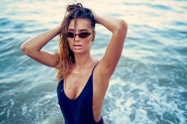 Ritratto di bella donna sexy caucasica ha preso il sole in occhiali da sole con i capelli lunghi in costume da bagno sdraiato sulla spiaggia d'estate