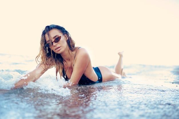 Ritratto di bella donna caucasica sexy prese il sole in occhiali da sole