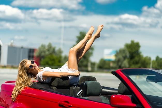 Ritratto di bella moda donna sexy moda in occhiali da sole seduto in lussuoso rosso convertibile auto con sfondo mare e cielo. giovane, donna, guida, viaggio, strada, soleggiato, estate, giorno. mare e cielo. cabrio rosso.