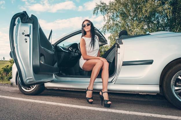 Ritratto di bella modella sexy della donna di modo in vestito bianco e accessori di lusso che si siedono in automobile di lusso. viaggio su strada. giovane donna che guida in viaggio su strada soleggiata giornata estiva.