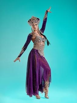 Il ritratto di bella giovane donna castana alla moda sexy con trucco luminoso con gioielli d'oro. cleopatra