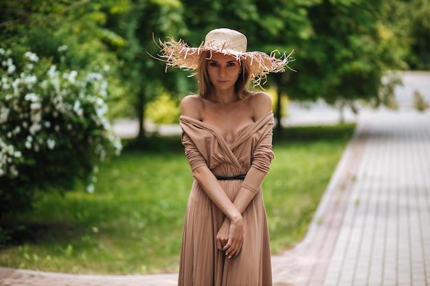 Ritratto di una bella donna sexy in un vestito con una scollatura e un cappello di paglia in un parco estivo